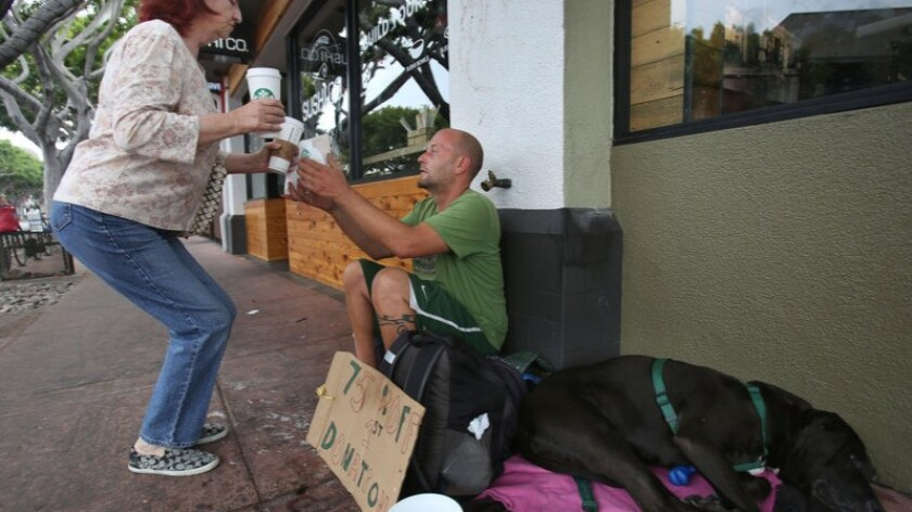 Jason Goodman reaches up to take a coffee and sandwich from local resident Fay Bowermaster outside a Starbucks outlet in San Diego's Hillcrest neighborhood.