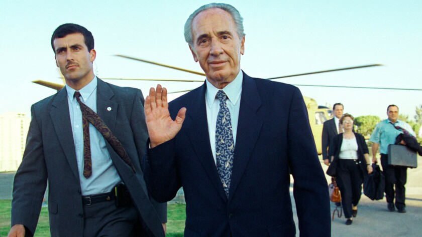 Shimon Peres, then the Israeli Minister of Foreign Affairs, waves to a photographer after returning from a visit to Jordan on July 20, 1994.