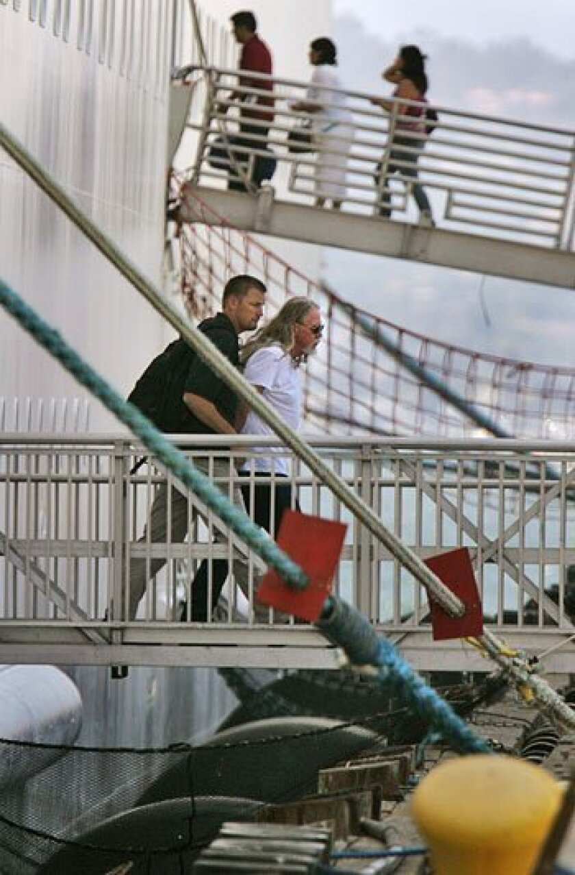 An FBI agent escorted Robert McGill of Los Angeles from a Carnival cruise ship docked in San Diego after his arrest in July 2009.