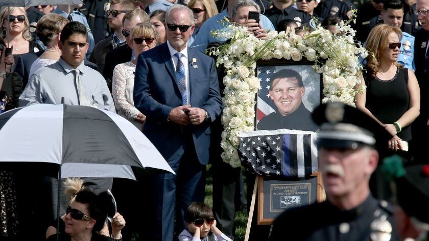 WHITTIER, CALIF. - MAR. 3, 2017. Mourners attend the burial of Whittier police officer Keith Wayne