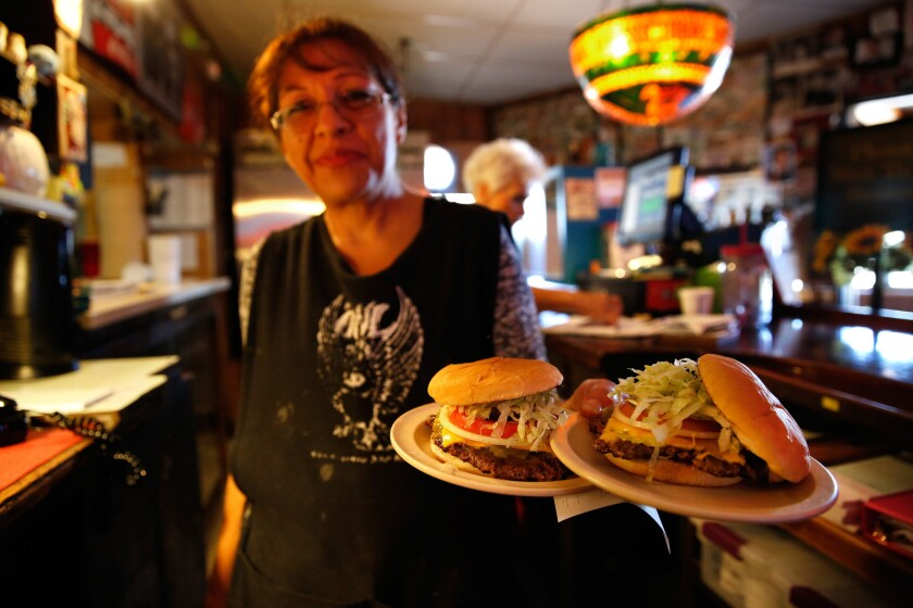 Waitress Patricia Moya delivers hot green chile cheeseburgers at the Owl Bar and Cafe in San Antonio, N.M.
