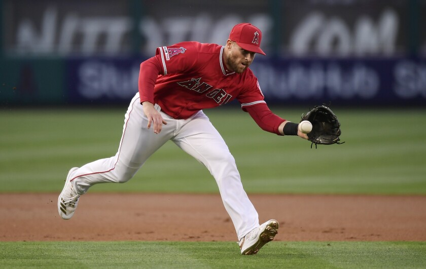 FILE - In this Saturday, May 25, 2019, file photo, Los Angeles Angels third baseman Zack Cozart fields a ball hit by Texas Rangers' Shin-Soo Choo, throwing him out at first, during the first inning of a baseball game in Anaheim, Calif. The San Francisco Giants bolstered their infield Tuesday, Dec. 10, 2019, by acquiring Cozart and prospect Will Wilson from the Los Angeles Angels for a player to be named or cash. (AP Photo/Mark J. Terrill, File)