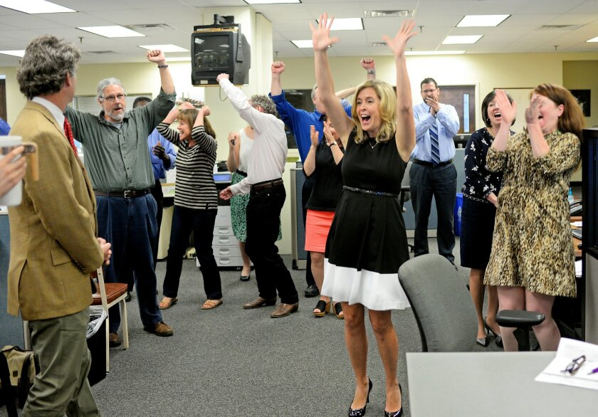 The Post and Courier staff, including publisher P.J. Browning, cheers after the Pulitzer announcement Monday, April 20, 2015 in Charleston, S.C. The newspaper was awarded a Pulitzer Prize for Public Service for its series on domestic violence. The Public Service gold medal went to reporters Doug Pa