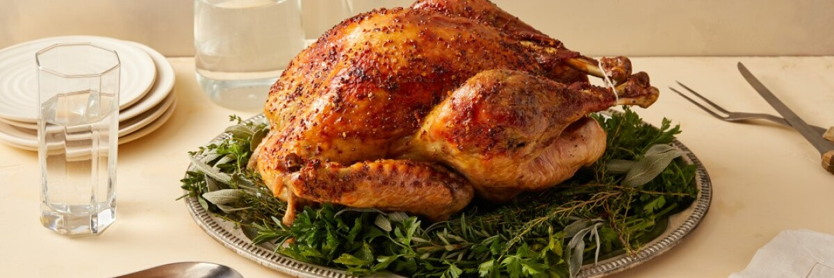 A whole turkey on a silver platter sits atop a dining table alongside a filled gravy boat.