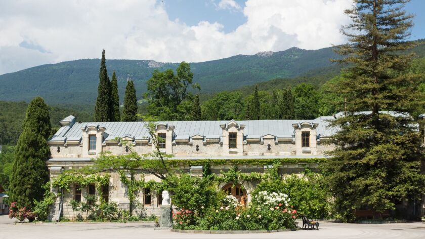 """the Facade of one of buildings of the wine factory """"Massandra"""" in the Crimea on the background of beautiful mountains"""