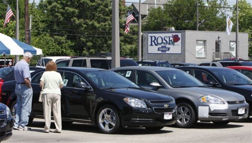 A couple looks over a new car on the lot of Rose Chevrolet, Sunday, May 31 2009, in Hamilton, Ohio. (AP Photo/David Kohl)
