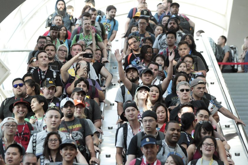 The first people in line for the exhibit hall cheer as they come down the escalator during Comic-Con's Preview Night at the San Diego Convention Center in San Diego on Wednesday.