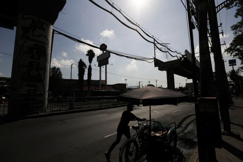 Un vendedor empuja su bicicleta más allá de la sección faltante de un metro elevado en la Ciudad de México