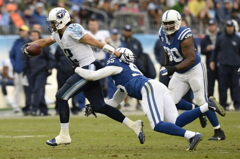 Tennessee Titans quarterback Charlie Whitehurst (12) is brought down by Indianapolis Colts outside linebacker Shaun Phillips (55) while scrambling for a 3-yard gain in the first half of an NFL football game Sunday, Dec. 28, 2014, in Nashville, Tenn. (AP Photo/Mark Zaleski)