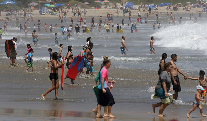 Hundreds of beachgoers play in the shore break at Corona del Mar State Beach on Tuesday.