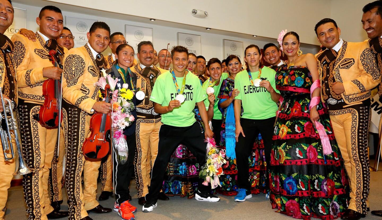 Los atletas Guadalupe González, Ismael Hernández (i), María del Rosario Espinoza y Germán Sánchez, con el mariachi, durante la recepción en el Aeropuerto Internacional de la Ciudad de México.