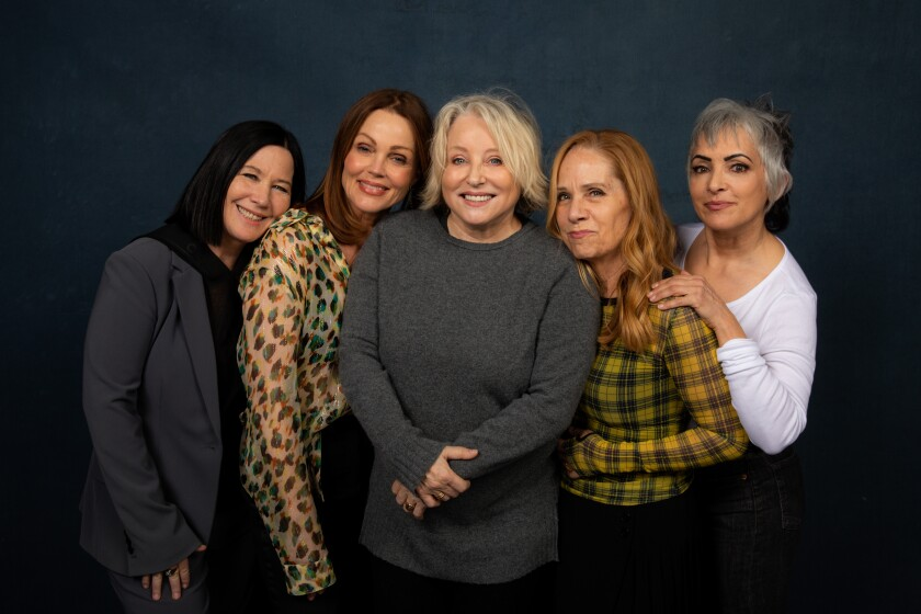Five women lean into each other