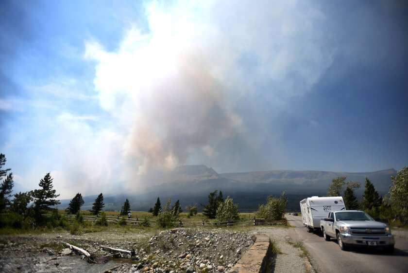 Visitors leave as part of a mandatory evacuation issued because of a wildfire Wednesday near East Glacier Park, Mont. The fire at Glacier National Park started Tuesday and has closed the eastern entrance.