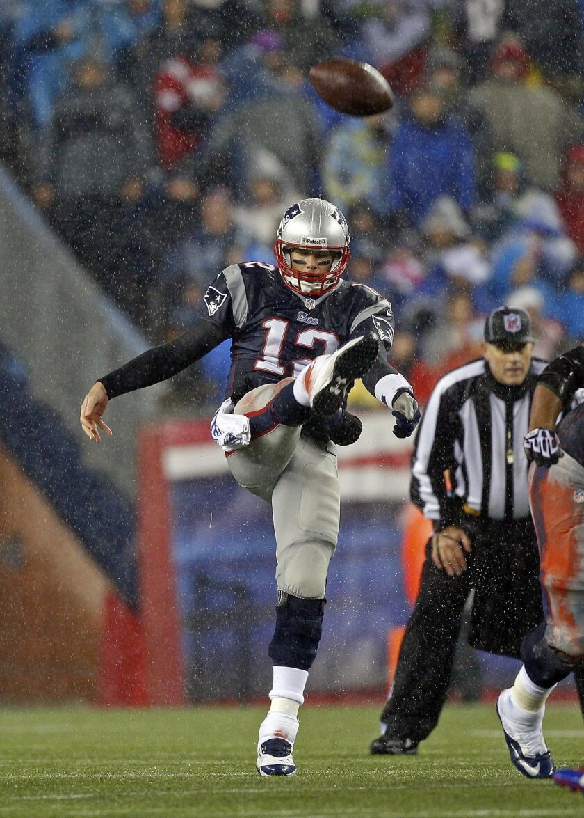 New England Patriots quarterback Tom Brady kicks a 32-yard punt on third down during the third quarter of an NFL football game against the Buffalo Bills, Sunday, Dec. 29, 2013, in Foxborough, Mass. The Patriots won 34-20, and will have a first-round bye in the AFC playoffs. (AP Photo/Boston Herald,