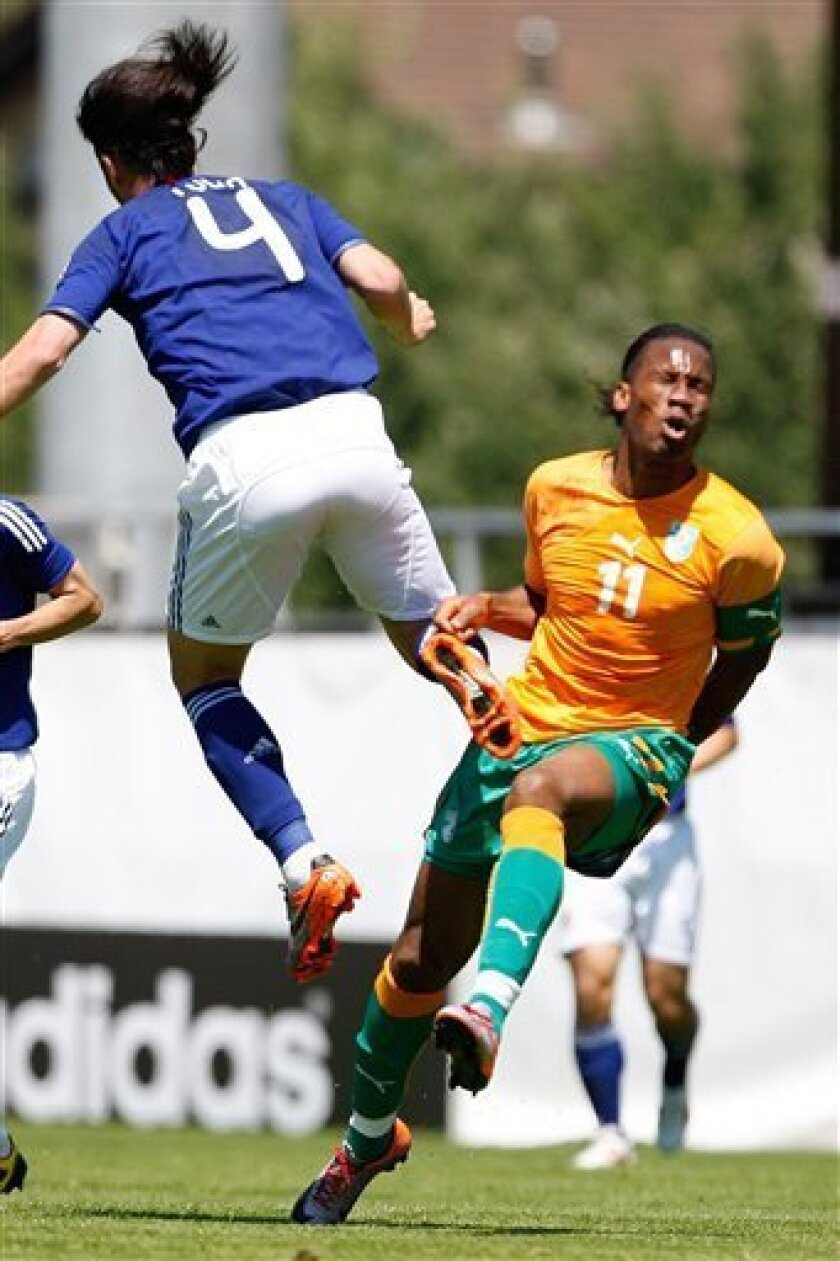 Ivory Coast forward Didier Drogba, right, is tackled by Japan's defender Marcus Tulio Tanaka, left, during an international friendly test game between the national soccer teams of Ivory Coast and Japan at the Stade de Tourbillon in Sion, Friday, June 4, 2010, ahead of the FIFA World Cup 2010 in South Africa. Ivory Coast will play in group G and Japan will play in group E. (AP Photo/Keystone/Jean-Christophe Bott)