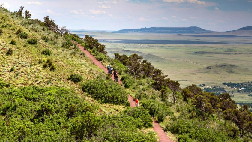 Tourists hiking on the Crater Rim Trail at Capulin Volcano National Monument in New Mexico.