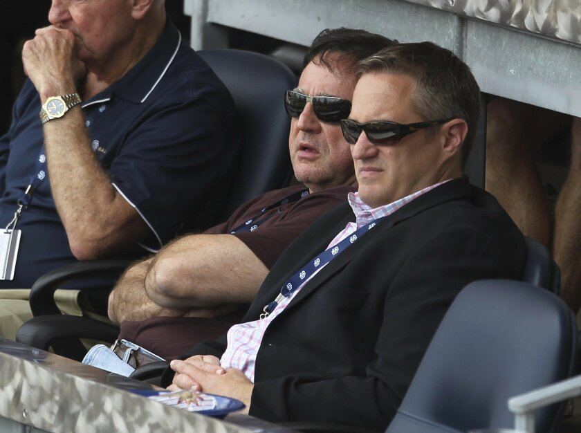 Padres majority owner John Moores and team CEO Tom Garfinkle watch a game played earlier this year against the Dodgers.