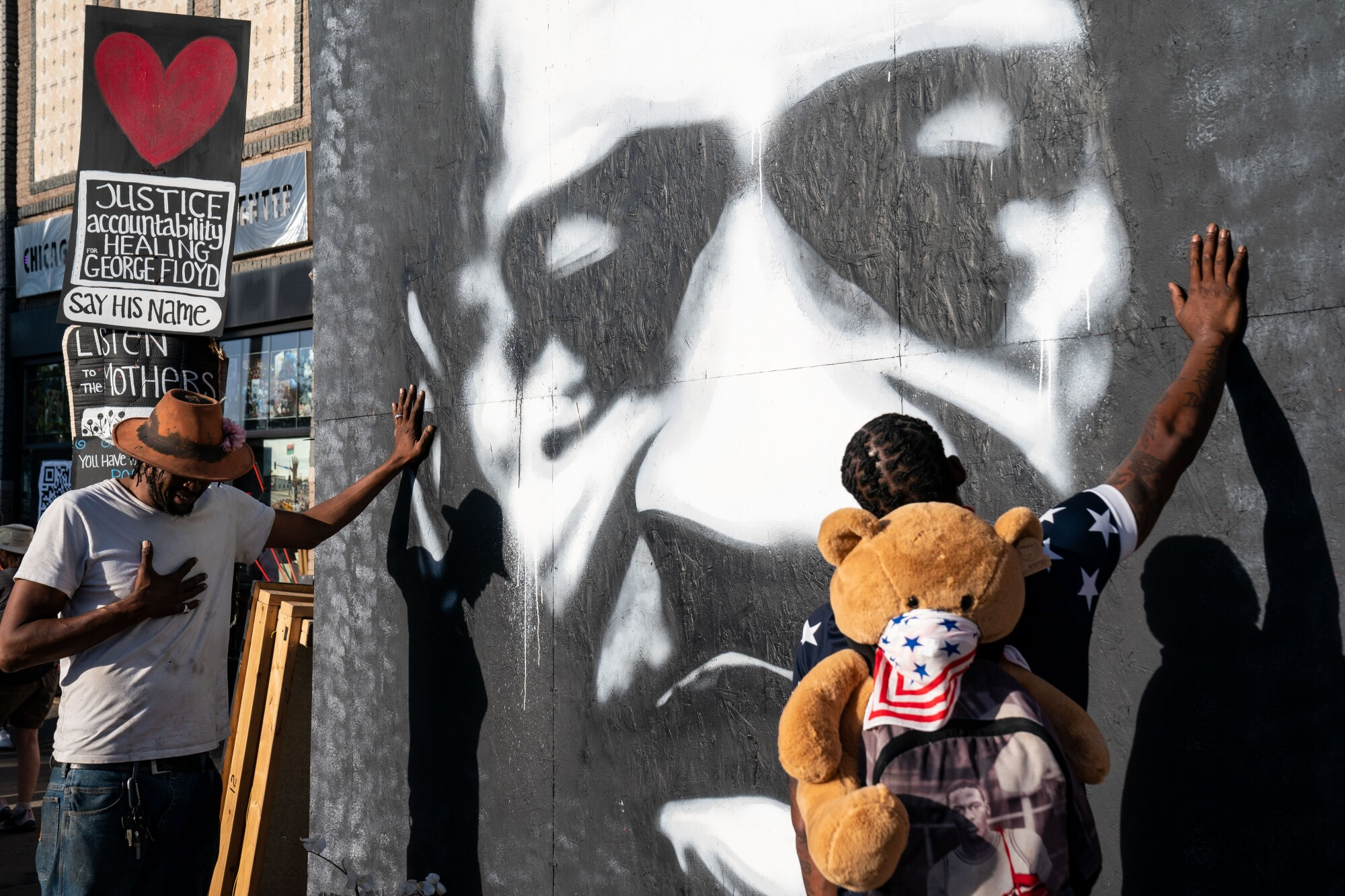 Two Black men place their hands on a mural depicting George Floyd