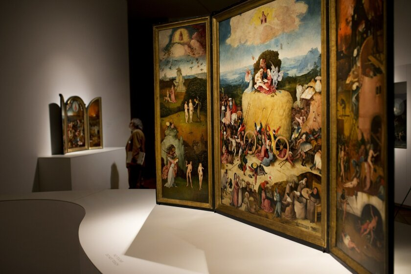 """In this Friday, May 27, 2016 photo, a man stands next to """"The Haywain"""" triptych painting, right, by Dutch artist Hieronymus Bosch during an exhibition at the Prado museum in Madrid, Spain. The exhibition for the 500th anniversary of Bosch that is billed as a once-in-a-lifetime review of the best an"""