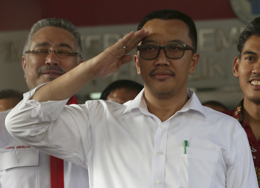 Indonesian Youth and Sports Minister Imam Nahrawi salutes after a press conference in Jakarta, Indonesia, Thursday, Sept. 19, 2019. Nahrawi has stepped down from his position after being named a bribery suspect by the country's anti-graft commission. (AP Photo/Tatan Syuflana)
