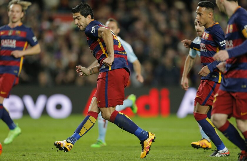 In this Sunday, Feb. 14, 2016 photo, FC Barcelona's Luis Suarez kicks the ball to score during a Spanish La Liga soccer match between FC Barcelona and Celta Vigo at the Camp Nou stadium in Barcelona, Spain. Lionel Messi put on another show at the Camp Nou on Sunday, scoring a remarkable goal from a