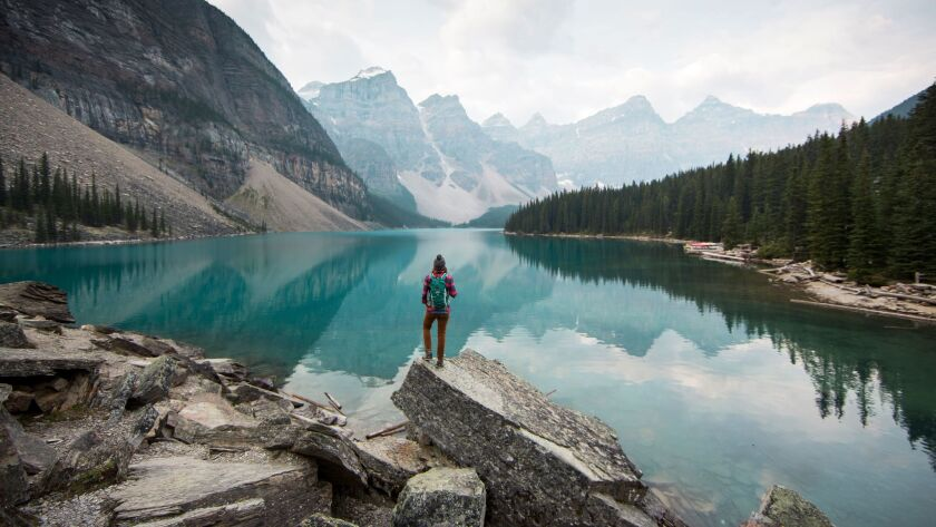 A woman stands on a scenic point overlooking Moraine Lake in Banff National Park in Alberta, Canada.