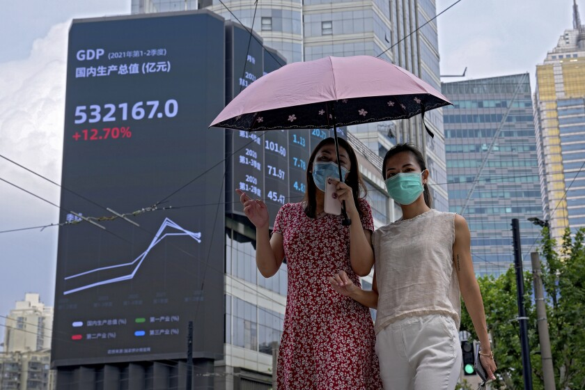 FILE - In this Aug. 24, 2021, file photo, women wearing face masks to help curb the spread of the coronavirus walk by an electronic billboard showing China's Gross Domestic Product (GDP) index on a commercial office building in Shanghai, China. Developing economies in Asia will likely grow at a slower pace than earlier expected due to prolonged COVID-19 outbreaks and uneven progress in vaccinations, the Asian Development Bank said in a report Wednesday, Sept. 22, 2021.( (AP Photo/Andy Wong, File)