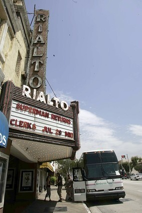 Members of a a 50-person bus tour of five Los Angeles-area historic theaters leave the bus at the Rialto Theatre in South Pasadena.