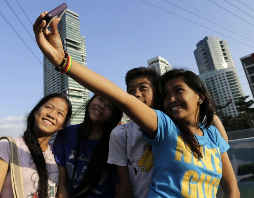 Filipino teens pose for a selfie group picture overlooking Makati City's skyline in the Philippines. The city has been dubbed the selfie capital of the world.