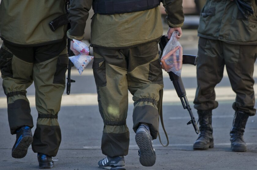 Russia-backed rebels hold food products while accompanying a bus carrying Ukrainian prisoners of war in Luhansk, Ukraine, Saturday, Feb. 21, 2015. Ukrainian military and separatist representatives exchanged dozens of prisoners under cover of darkness at a remote frontline location Saturday evening, kicking off a process intended to usher in peace to the conflict-ridden east. Ukrainian troops and rebels were exchanged, according to a separatist official overseeing the prisoner swap at a no man's land location near the village of Zholobok, some 20 kilometers (12 miles) west of the rebel-held city Luhansk. (AP Photo/Vadim Ghirda)