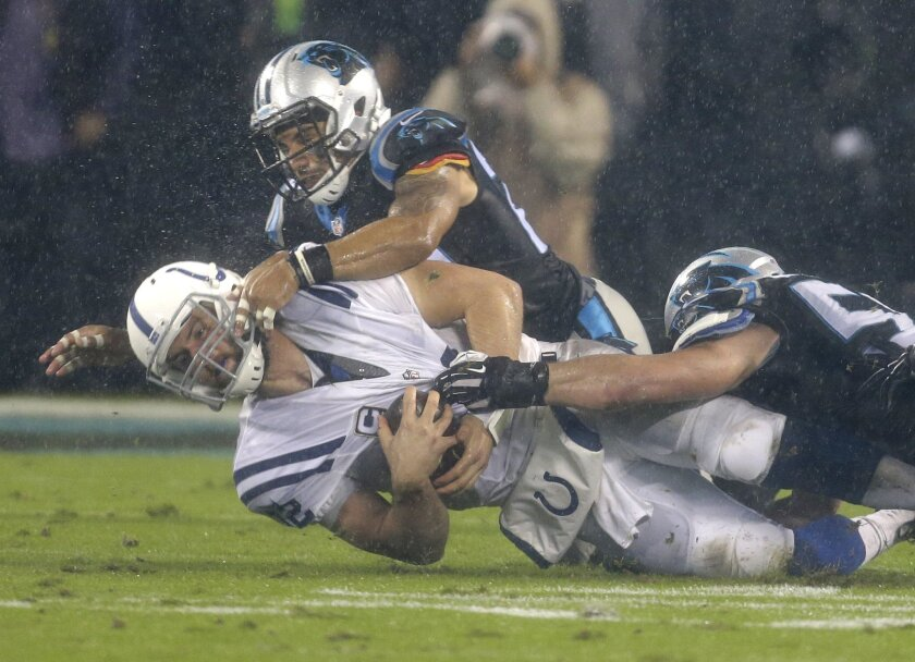 Indianapolis Colts' Andrew Luck, center, is tackled by Carolina Panthers' Luke Kuechly, right, and Kurt Coleman, left, in the first half of an NFL football game in Charlotte, N.C., Monday, Nov. 2, 2015. (AP Photo/Bob Leverone)