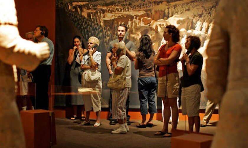 TERRA COTTA WARRIORS: Patrons use audio devices to learn about the Chinese fighting men from 210 BC. Attendance could top 200,000, outdistancing the Bowers Museum's previous record, set in 2000.
