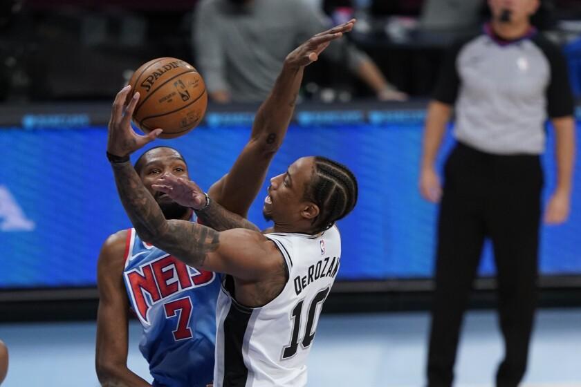 Spurs guard DeMar DeRozan elevates toward the basket against Nets forward Kevin Durant on a layup attempt.