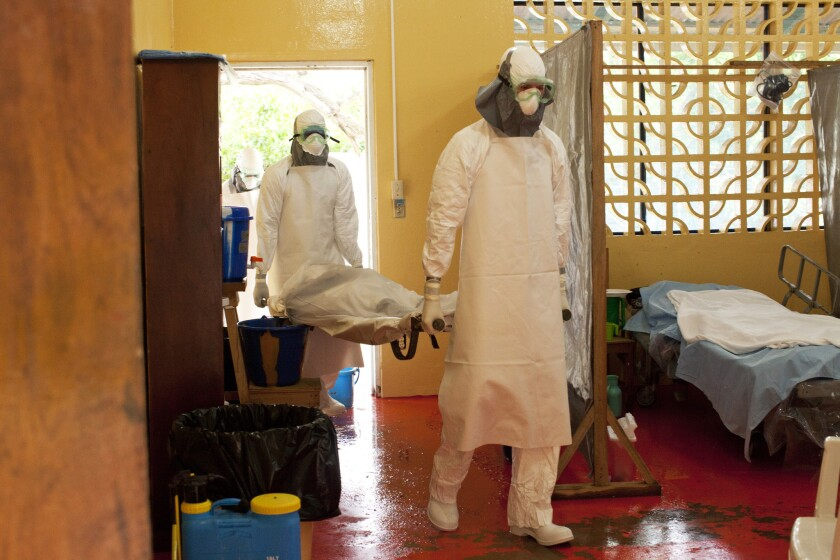 Two people in protective clothing carry a body at an Ebola isolation ward in Liberia.