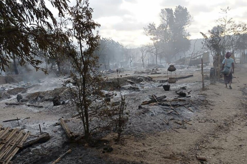 Una persona camina por unas casas humeantes en la aldea de Kinma, en el centro de Myanmar, el miércoles 16 de junio de 2021, luego de que unos soldados de la junta militar que gobierna el país quemaron gran parte del poblado. (AP Foto)