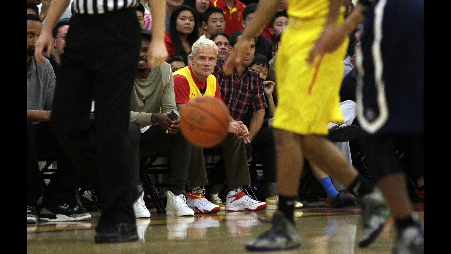 Flea, the bassist for the Red Hot Chili Peppers (yellow shirt), sits court side during the game between Sierra Canyon and Fairfax at Fairfax High School.
