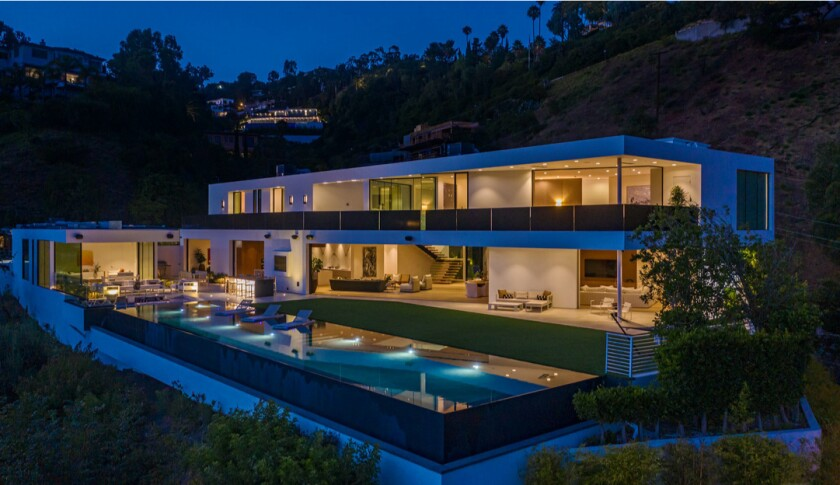 The 10,700-square-foot mansion in Benedict Canyon opens to a 100-foot saltwater pool with sweeping views of the city below.