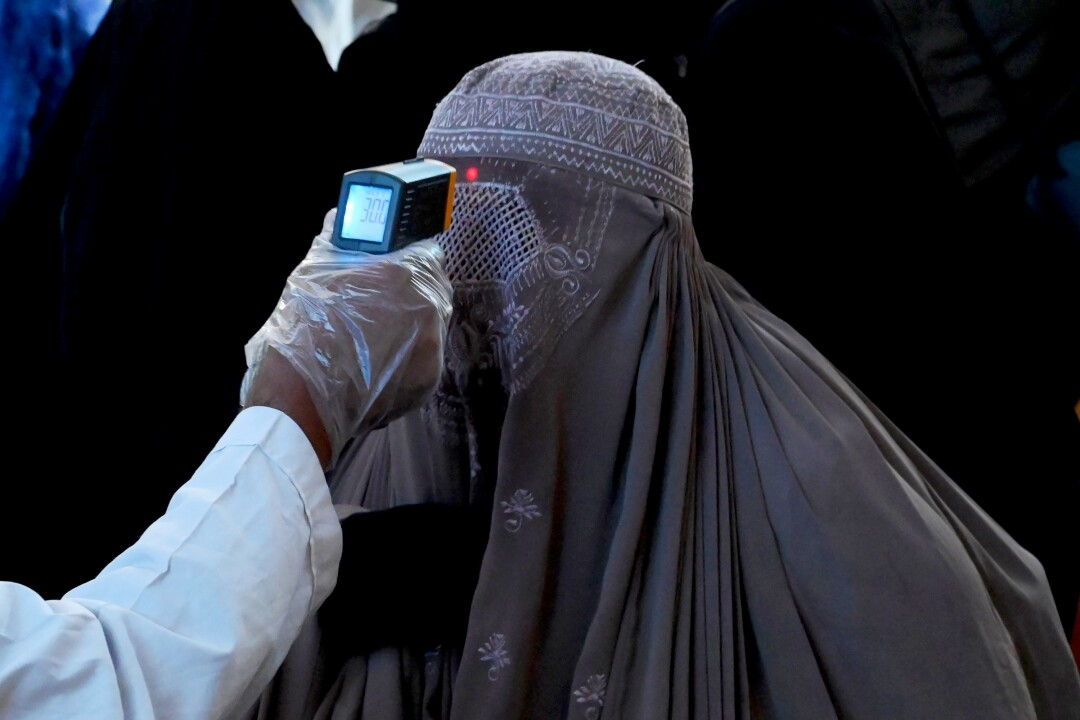 A health official checks a woman's temperature at a Pakistan railway station.