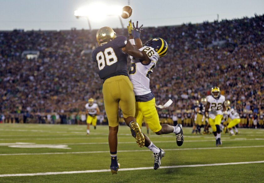 Michigan defensive back Jourdan Lewis, right, interferes with Notre Dame wide receiver Corey Robinson in as he attempts a catch in the end zone during the first half of an NCAA college football game in South Bend, Ind., Saturday, Sept. 6, 2014. (AP Photo/Michael Conroy)
