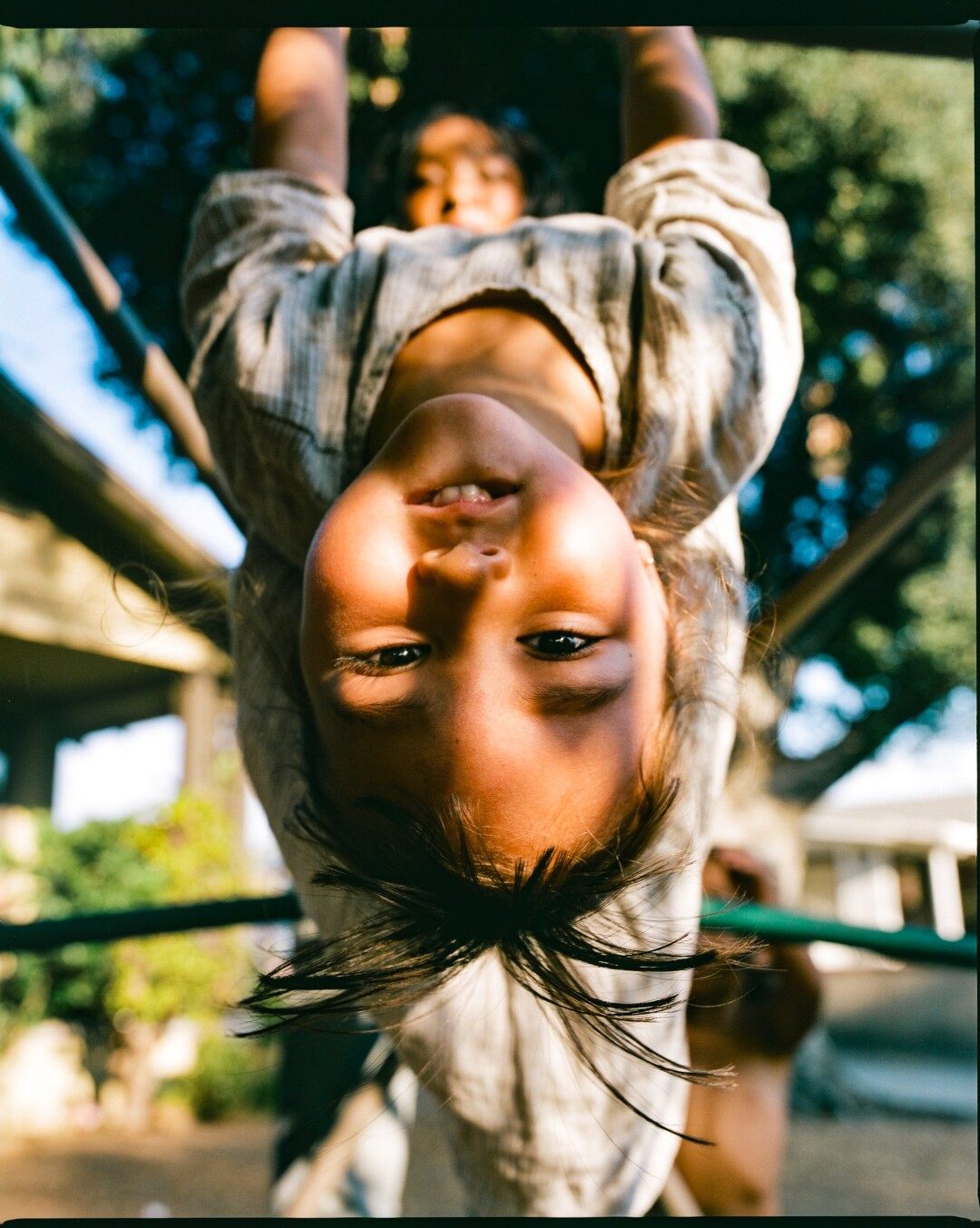 Synmia's daughter upside down on a jungle gym