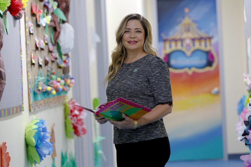 Alethea Arguilez holds colorful children's book, looking straight at camera
