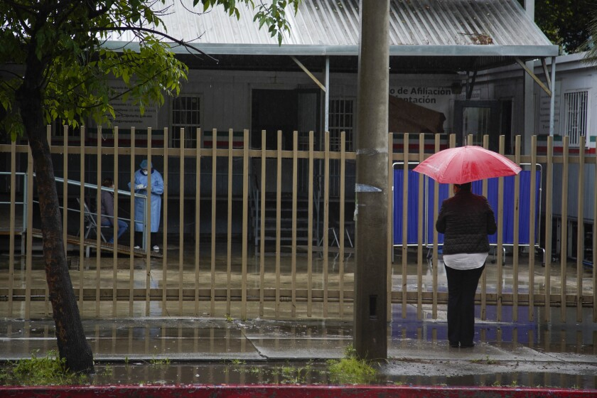 At Hospital General in Tijuana, a woman with a red umbrella watches as a patient is examined by hospital healthcare worker.