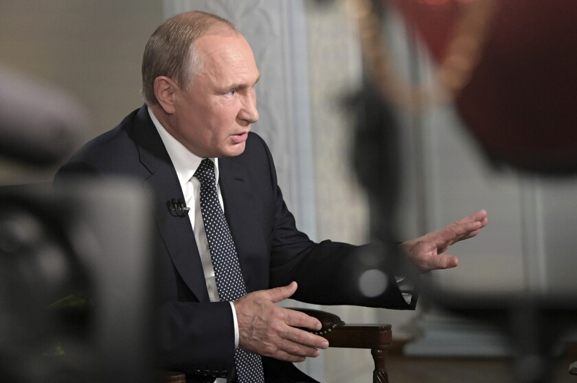 """Russian President Vladimir Putin gestures during an interview with """"Fox News Sunday"""" host Chris Wallace after his meeting with U.S. President Donald Trump in Helsinki, Finland, on July 16, 2018."""