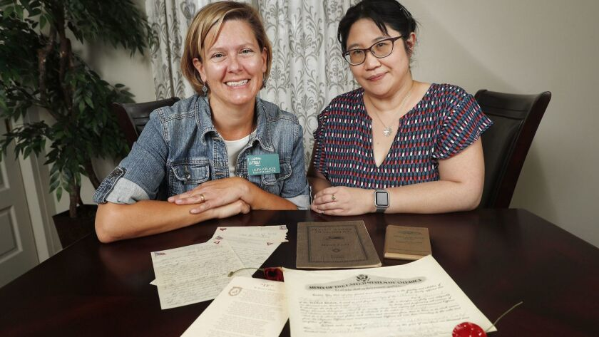 Executive Director Laura Verlaque and Archivist Julie Yamashita with documents and a diary from Lloy