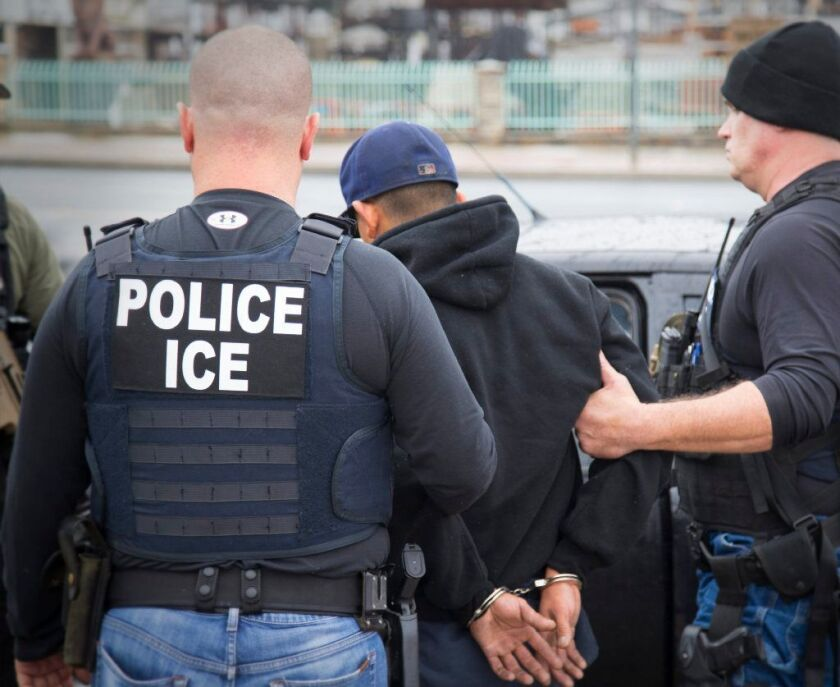 U.S. Immigration and Customs Enforcement officials take a person into custody.