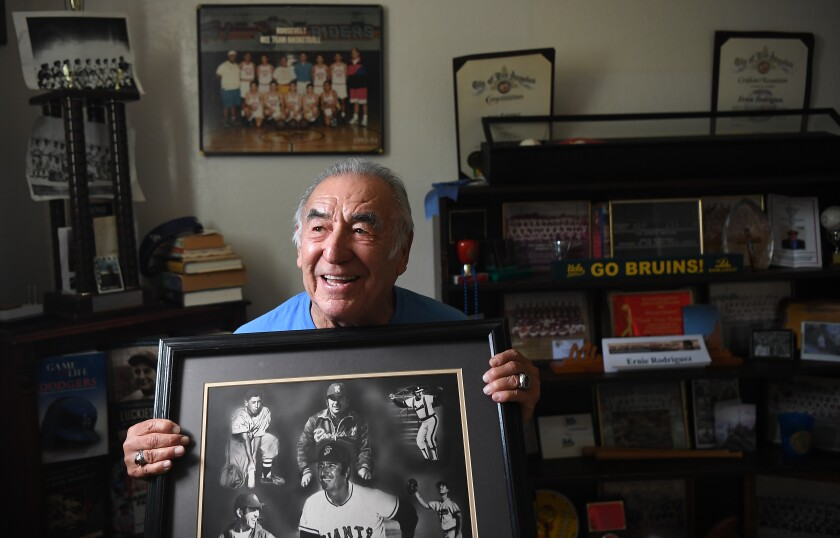 Ernie Rodriguez, an outfielder who debuted with the Chorizerosat 16, shows a mural from his playing and coaching days.