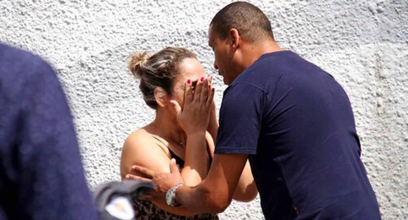 Un hombre conforta a una mujer en las afueras de la Escuela Estatal Raul Brasil en Suzano, Brasil, donde . dos adolescentes con capuchas abrieron fuego en una escuela pública.