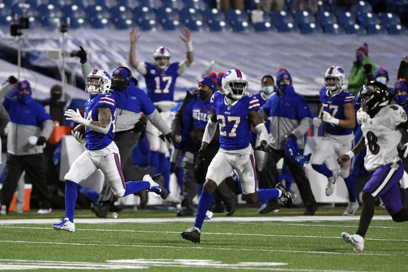 Buffalo Bills cornerback Taron Johnson, left, runs away from Baltimore Ravens quarterback Lamar Jackson (8) after intercepting his pass for a touchdown during the second half of an NFL divisional round football game Saturday, Jan. 16, 2021, in Orchard Park, N.Y. (AP Photo/Adrian Kraus)