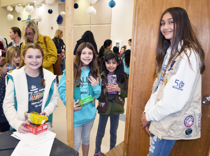 Junior Girl Scouts Sofia Maas and Bianca Cox, along with Brownie Isabel Portales, practice how they will conduct door-to-door sales with Cadette Ellie Smith at the cookie kickoff in Poway on Jan. 17.