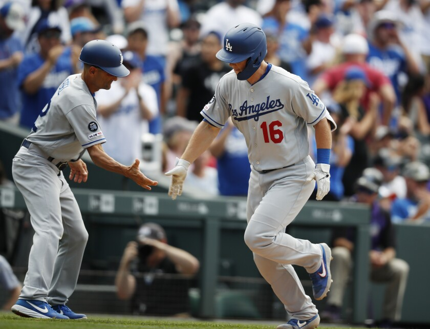 Dodgers third base coach Dino Ebel, left, congratulates Will Smith as he circles the bases after hitting a three-run home run off Colorado Rockies relief pitcher Wade Davis in the ninth inning on Wednesday in Denver.
